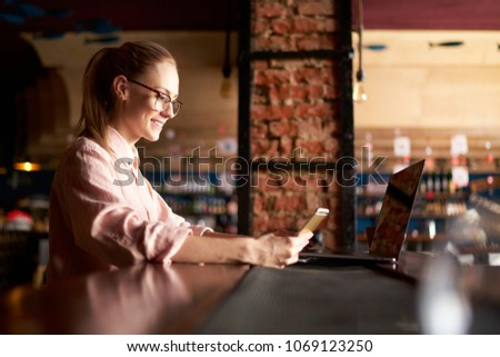 Happy woman working using multiple devices on a desk. Happy woman with laptop at cafe checking her emale box. administrative manager holding cellular reading text for meeting #1069123250