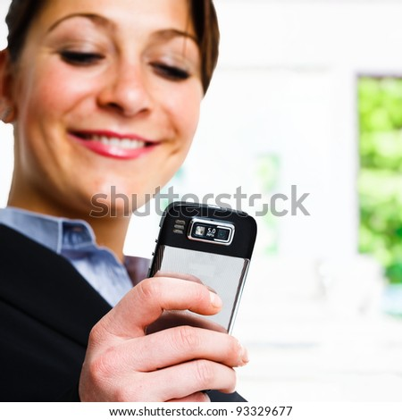 Happy woman writing a text message