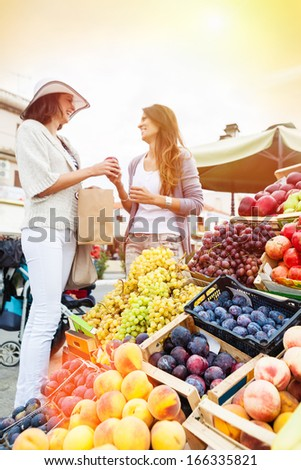 Happy women choosing a fruit outdoors in the bio market,sunset light. Focus on the grape. Lens flare