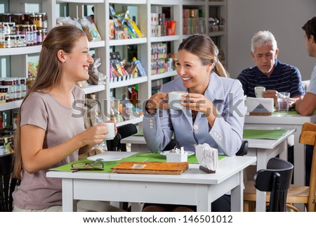 Happy women communicating while having coffee at supermarket