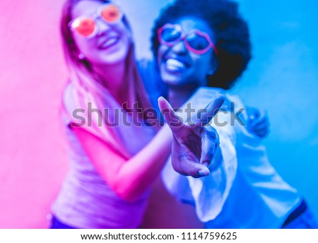 Happy women friends making party outdoor - Trendy girls with sunglasses having fun laughing together - Youth and friendship concept - Focus on african female face - Blue and purple radial filter