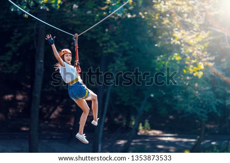 Happy women girl female gliding climbing in extreme road trolley zipline in forest on carabiner safety link on tree to tree top rope adventure park. Family weekend children kids activities concept
