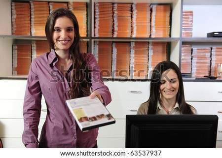 Happy women handing over dvd at the video rental store