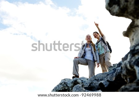 Happy women hikers stand on top of a rock and admire the view