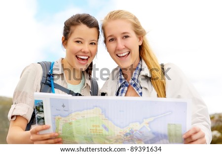 Happy women hold map and laugh. fun outdoor adventure lifestyle concept.