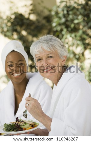Happy women in bathrobe eating