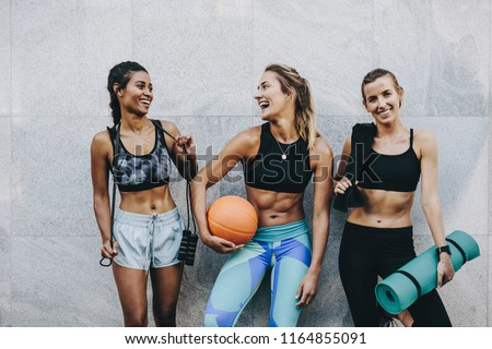 Happy women in fitness clothes relaxing and having fun standing against a wall. Fitness women carrying skipping rope basketball and workout mat standing after workout. #1164855091