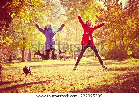 happy women jumping outside at autumn fall