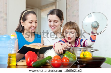 Happy women of three generations cook vegetables in the kitchen at home