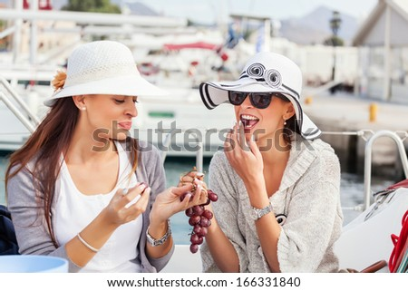 Happy women on the bow of a Sail boat eating a grapes fruit. #166331840