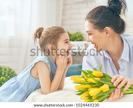 Happy women's day! Child daughter is congratulating mom and giving her flowers tulips. Mum and girl smiling and hugging. Family holiday and togetherness. #1024469230