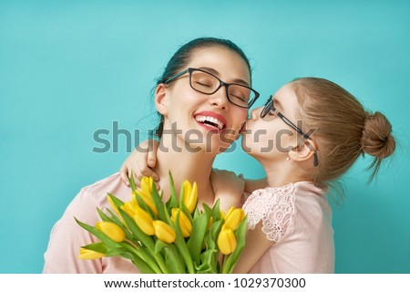 Happy women's day! Child daughter is congratulating mom and giving her yellow flowers tulips. Mum and girl smiling and hugging on light blue background. Family holiday and togetherness. #1029370300