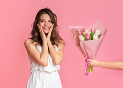 Happy Women's Day Concept. Excited young girl in cocktail dress getting bouquet of tulips as gift, touching cheeks in joy, standing on pink background