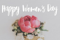 Happy women's day text sign on peony, white flowers and eucalyptus in craft envelope on white wood. 8 march International women's day. Stylish floral greeting card, handwritten greetings