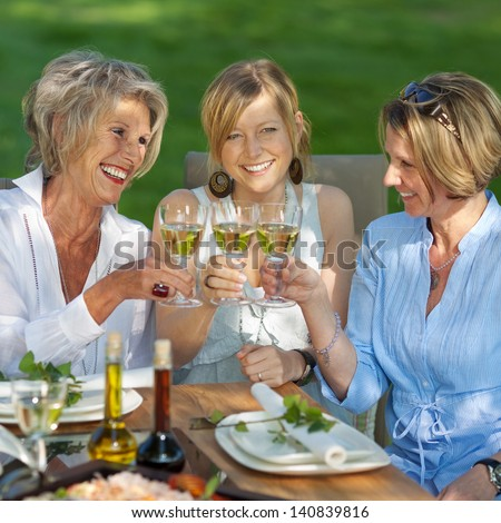 happy women saying cheers with white wine at the garden party