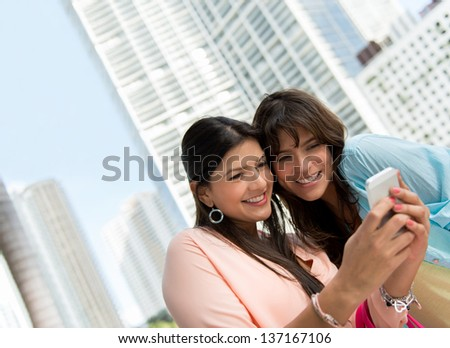 Happy women using an app on a smart phone