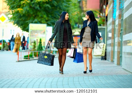 happy women walking the city street with shopping bags