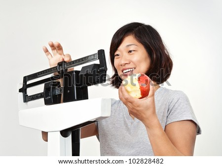 Happy women weighing herself on medical weight scale, smiling and pleased with her weight loss.