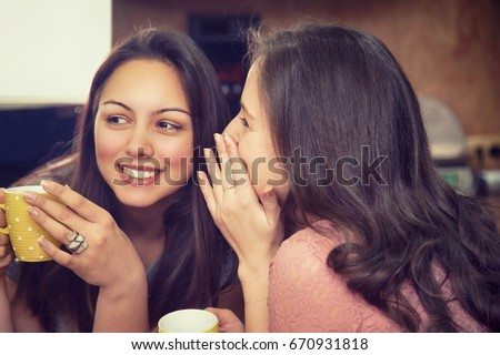 Happy women whispering and drinking coffee. Smiling girls telling secrets and gossiping.  Stock foto ©