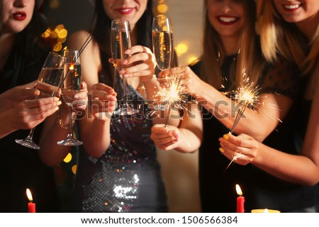 Happy women with Christmas sparklers and glasses of champagne at party