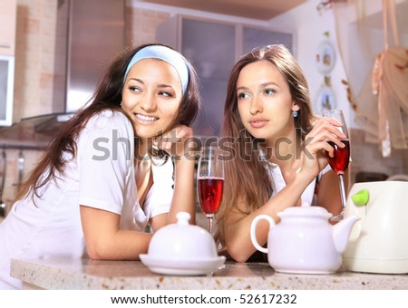Happy women with glasses of red wine talk about on kitchen