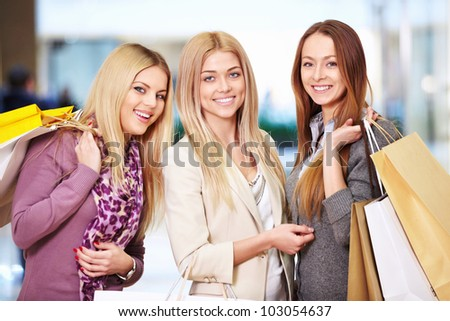 Happy women with shopping bags in store