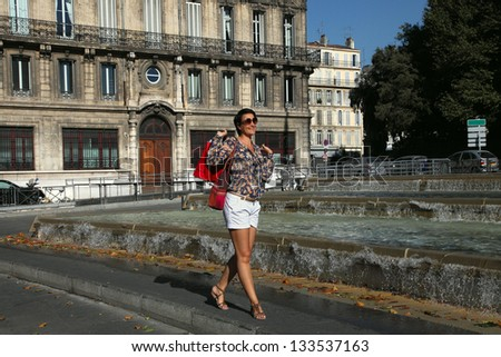 Happy women with shopping bags walking in the city - stock photo