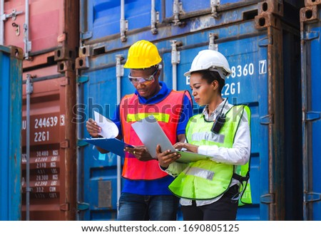Happy worker man in hardhat and safety vest holding clipboard checklist and Female foreman using laptop control loading containers box from cargo Zdjęcia stock ©