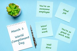 Happy World Compliment Day. Office desk with plant, notebook, pen and paper slips with compliments text for office worker such as GOOD JOB. Greeting card for world compliment day. Flat lay, top view