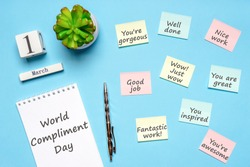 Happy World Compliment Day. Office desk with plant, notebook, pen and paper slips with compliments text for office worker such as GOOD JOB. Calendar date 1 March, greeting card. Flat lay, top view