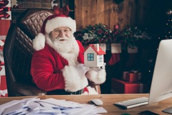 Happy x-mas christmas season shopping sales. Jolly white grey beard hair santa claus sit table hold small insurance building wear cap in house indoors with spirit atmosphere advent tinsels