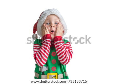Happy Xmas and New Year holiday! Shocked and surprised kid with red Christmas hat with head in hands. Cheerful smiling little boy opens his mouth in surprise. #738183715