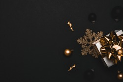 Happy xmas. White gift box with golden ribbon, New Year balls and sparkling lights garland in Christmas composition on black background for greeting card. Copy space. Winter holidays, New Year.