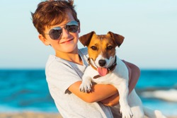 Happy 8 year old boy hugging his dog breed Jack russell at the seashore against a blue sky close up at sunset. Best friends rest and have fun on vacation, play in the sand against the sea