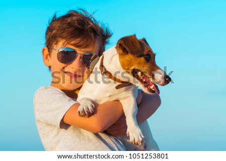 Happy 8 year old boy hugging his dog breed Jack russell at the seashore against a blue sky close up at sunset. Best friends rest and have fun on vacation, play in the sand against the sea #1051253801
