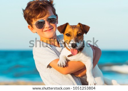 Happy 8 year old boy hugging his dog breed Jack russell at the seashore against a blue sky close up at sunset. Best friends rest and have fun on vacation, play in the sand against the sea #1051253804