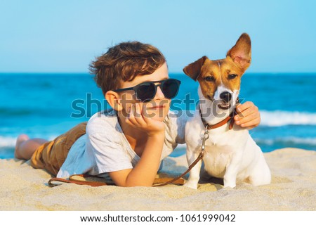 Happy 8 year old boy hugging his dog breed Jack Russell terrier at the seashore against a blue sky close up at sunset. Best friends rest and have fun on vacation, play in the sand against the sea