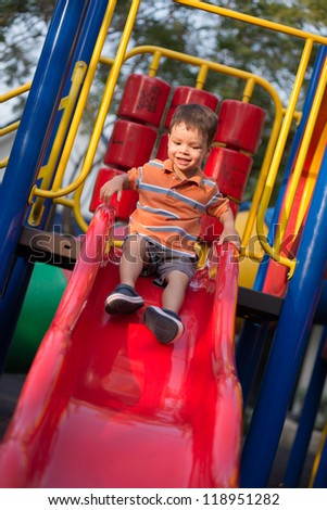 Happy 2 year old boy riding a red slide in an outdoor playground