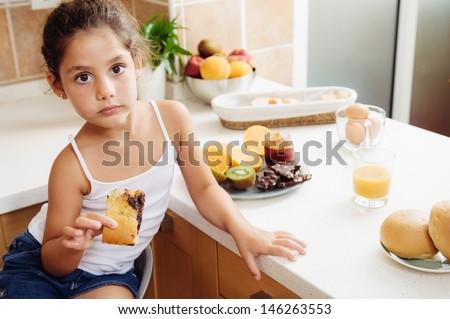 Happy 5 year old girl over breakfast. It is part of a happy family. It is a healthy breakfast