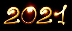 Happy 2021 year. Yellow nubmers created by light on the black background. Light painting photography, lettering