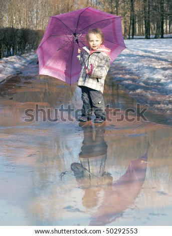 happy 2 years old girl with wellingtons and umbrella, little photo-joke with reflection
