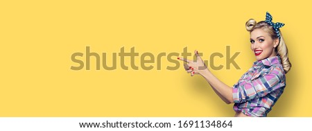 Happy young adorable woman pointing. Excited girl in pin up style, showing something or copy space for slogan or text. Retro fashion and vintage hairdo concept. Yellow background.
