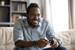 Happy young adult african american ethnicity guy gamer player holding gamepad controller playing video game sitting alone on couch in living room at home, console videogames hobby concept