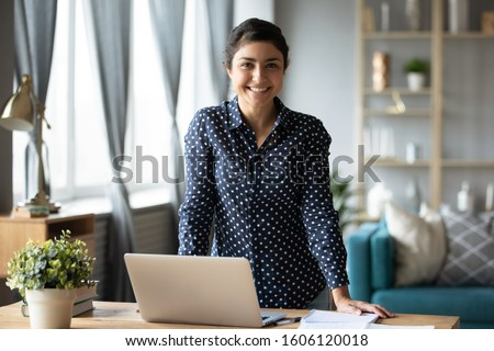 Happy young adult indian woman student freelancer teacher look at camera stand at home office table with laptop computer, online study concept, easy e learning in internet, education software tech