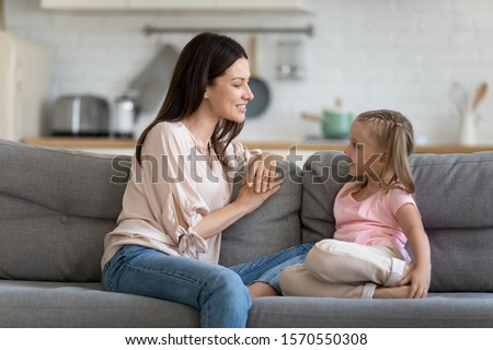 Happy young adult mother and cute child enjoy talking relaxing sit on sofa, understanding mom friend having sincere conversation with little daughter at home, trust in parent kid relationship concept