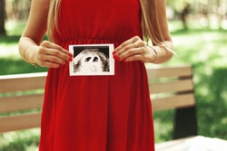 Happy young adult pregnant girl holds in her hands a snapshot of an ultrasound scan of a child. Twins. Two fetal eggs. First trimester
