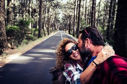 Happy young adult travel couple together with love and friendship enjoy the road and walking in the nature woods forest - selfie and woman smile hugging man in relationship adventure outdoor
