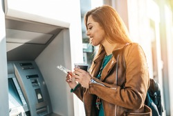 Happy young adult woman standing in front of ATM machine, smiling and holding credit or debit card.