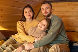 Happy young affectionate father, mother and little daughter in casualwear sitting on sofa inside country house and looking at you with smiles