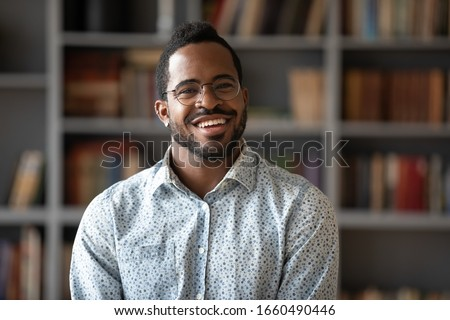 Happy young african american businessman entrepreneur in glasses, head shot portrait. Smiling millennial biracial man in eyewear looking at camera, posing for photo in modern office, library or home.